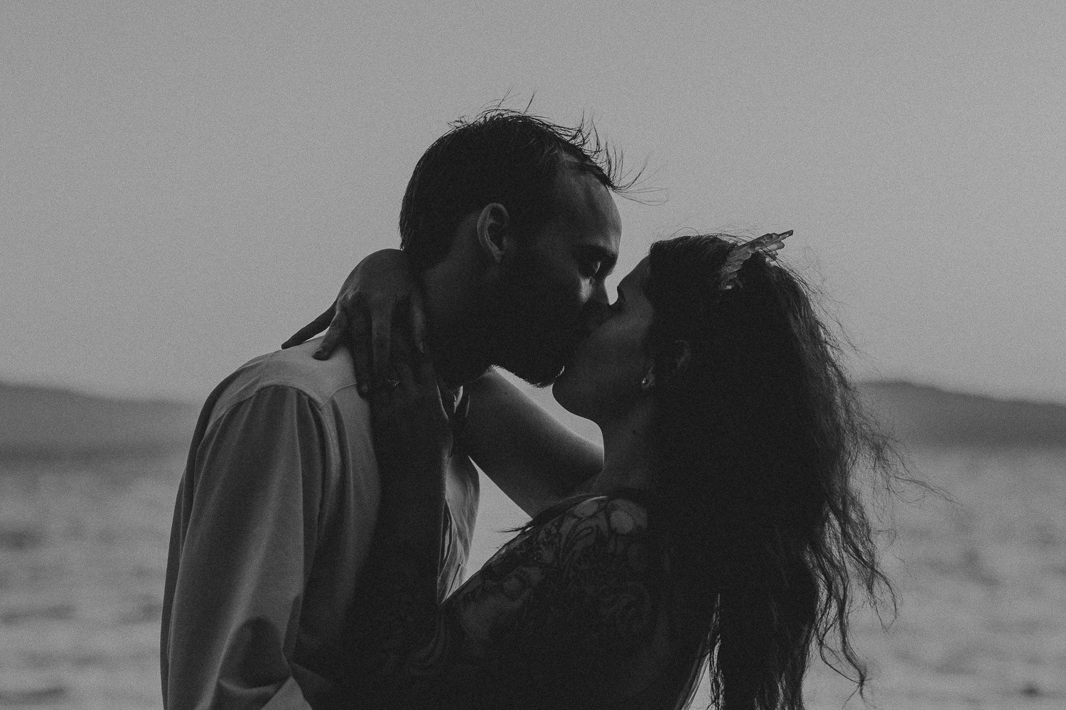 Black and White image of groom kisses bride