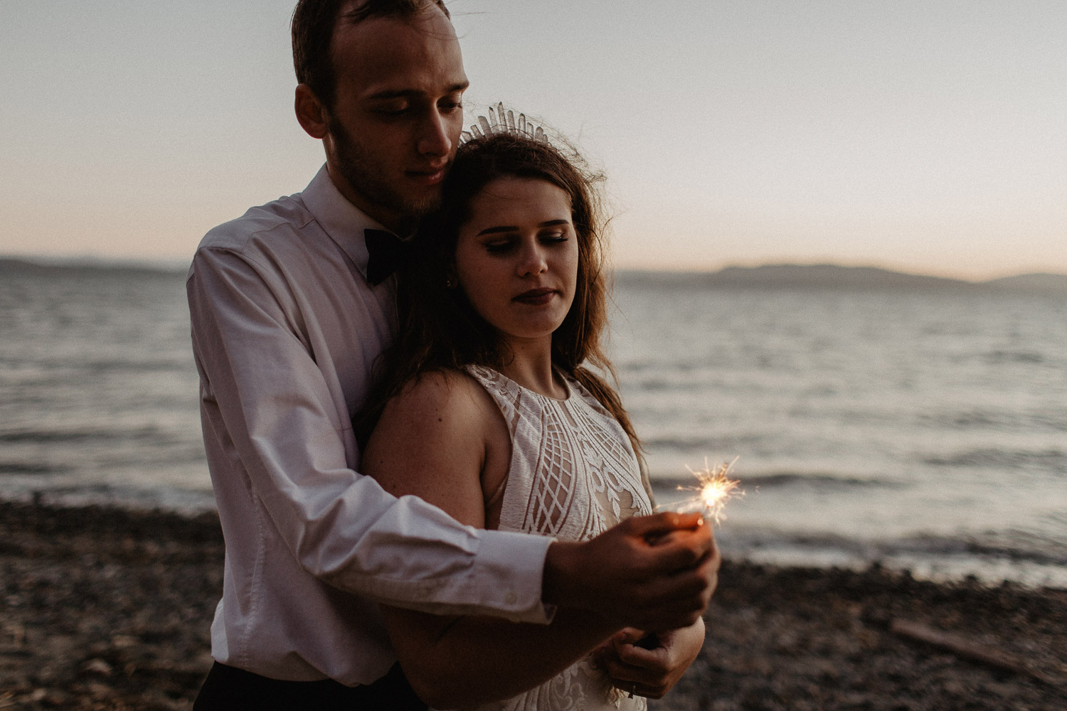 Image of groom and bride burn a sparkler together on the beach