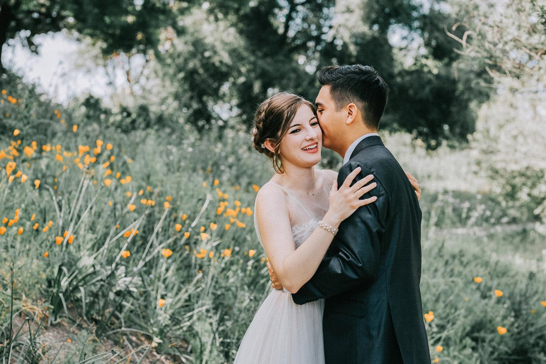 Image of groom kisses bride on cheek
