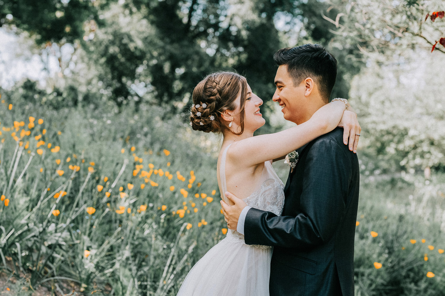 Image of groom and bride smile at each other