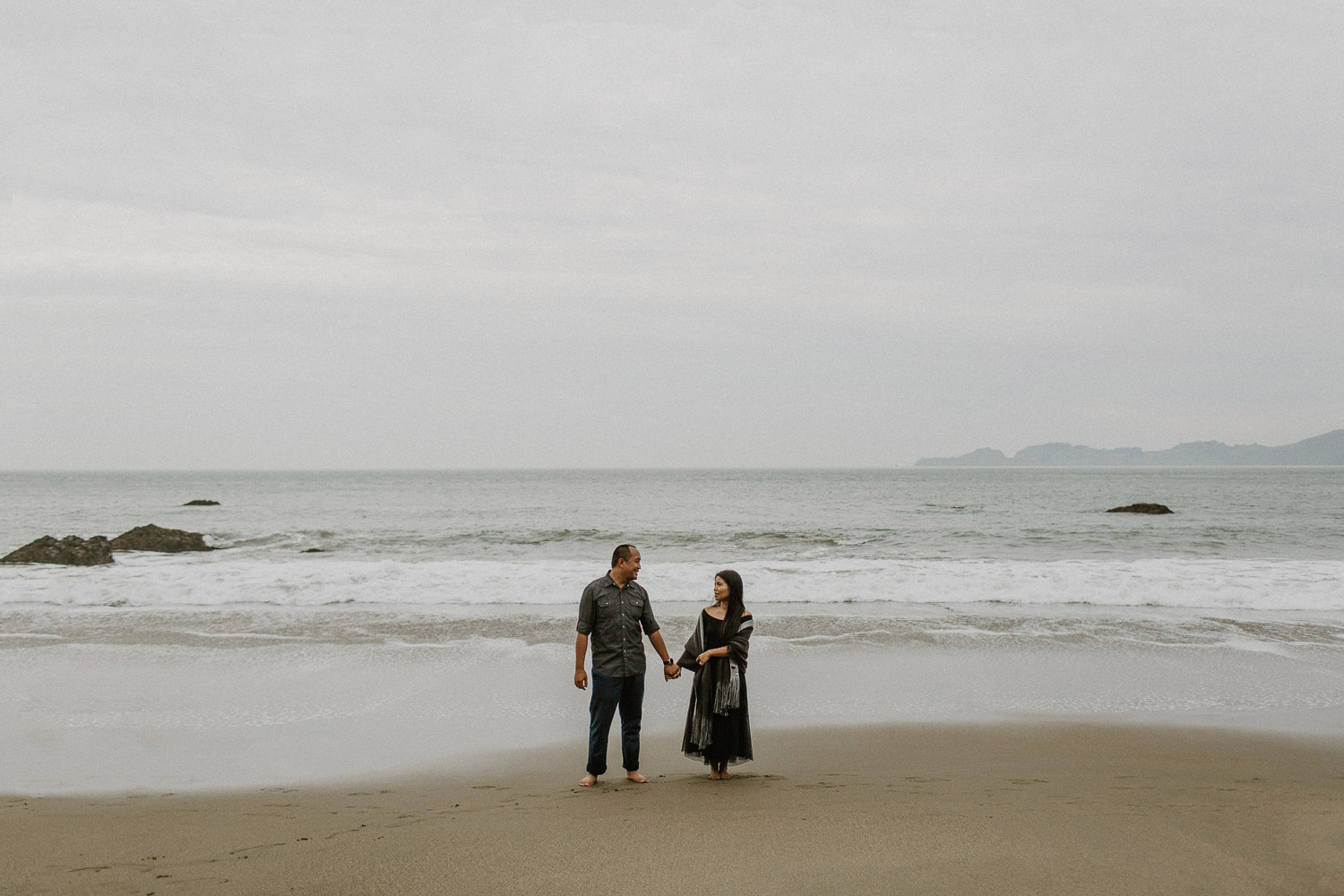Image of Asian Couple Holds Hands Together and Stands on the Beach