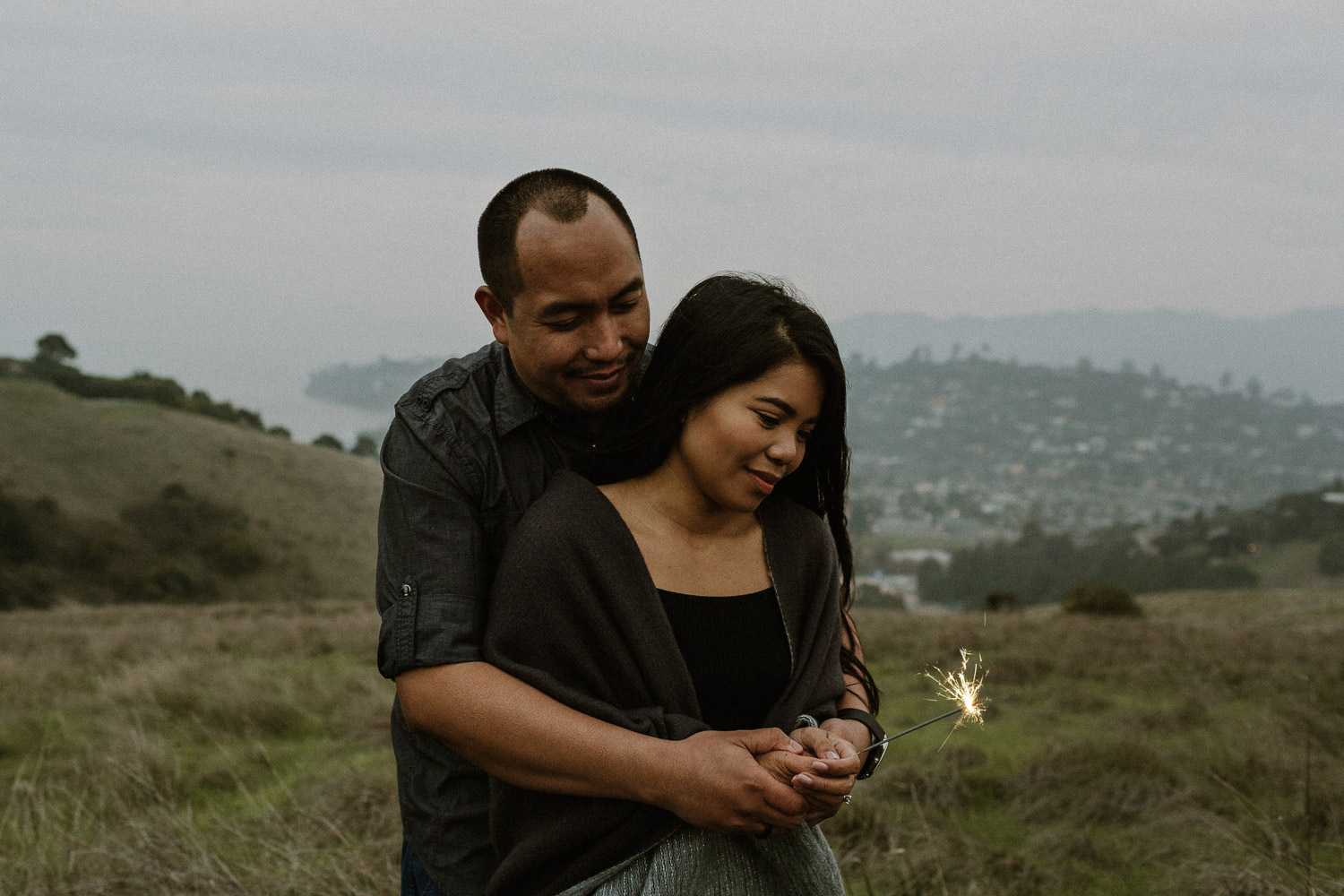 Image of Asian Couple Light Up a Sparkler Together on the Hill