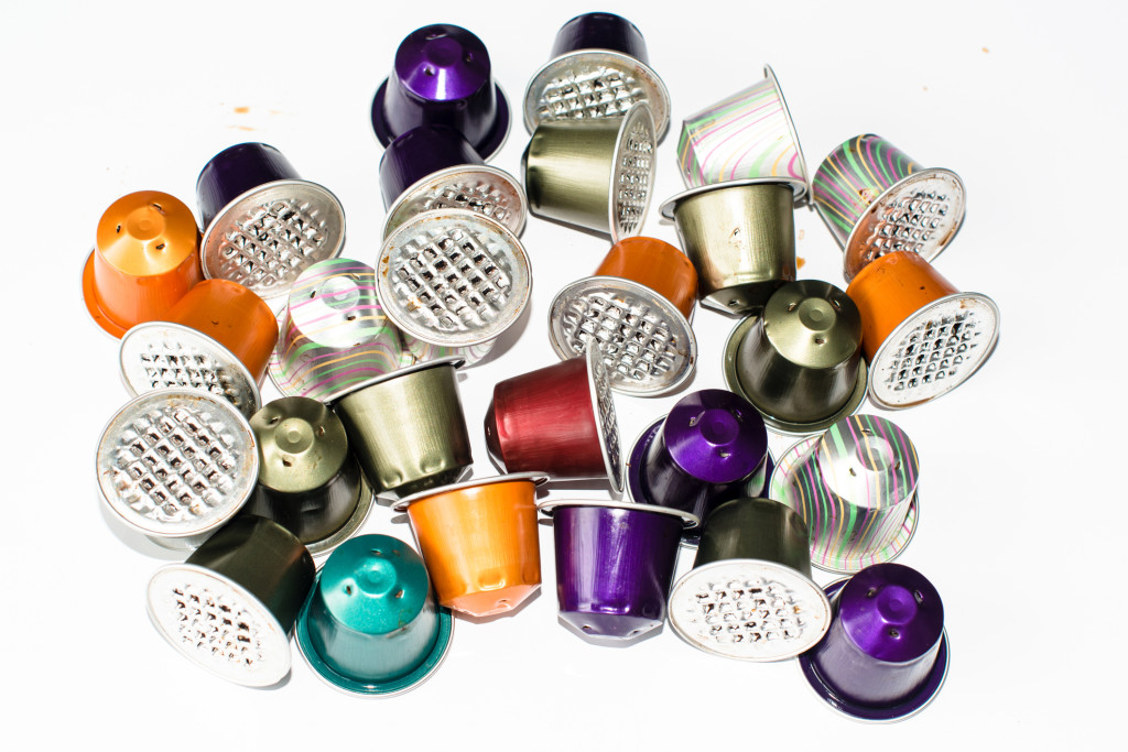 Colourful used gourmet coffe capsules on a bright reflective background