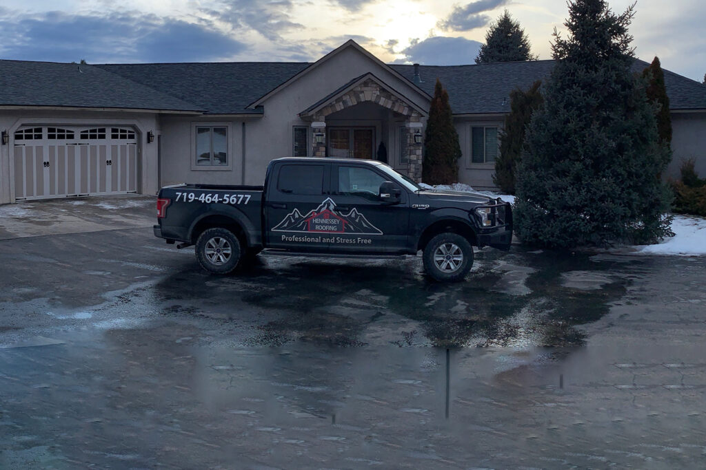 Hennessey Roofing Truck Parked in Front of Beautiful Black and Gray Roof in Colorado Springs