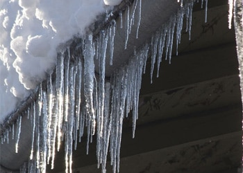 Icicles and Heavy Wet Snow clinging to a roof in Colorado Springs, CO
