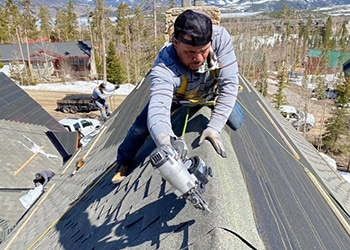 Hennessey Roofing Crew at work on top of a roof in Breckenridge, CO