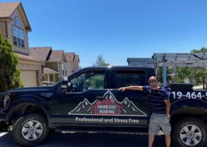 Scott Bauer posing with the Hennessey Roofing Truck in Colorado Springs
