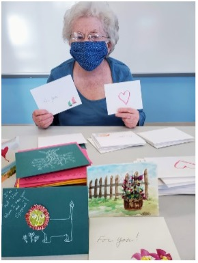 Peg Rose displays member-created Valentine's for the Harwich COA