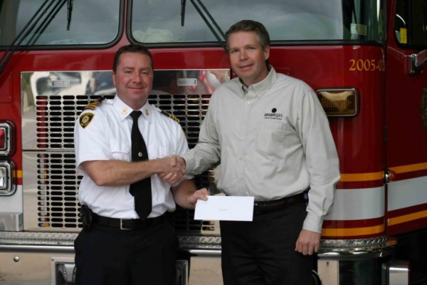 Deputy Chief Jim Jessop accepts donation from Ian Ross of Union Gas. (Photo courtesy of the City of London Fire Department)