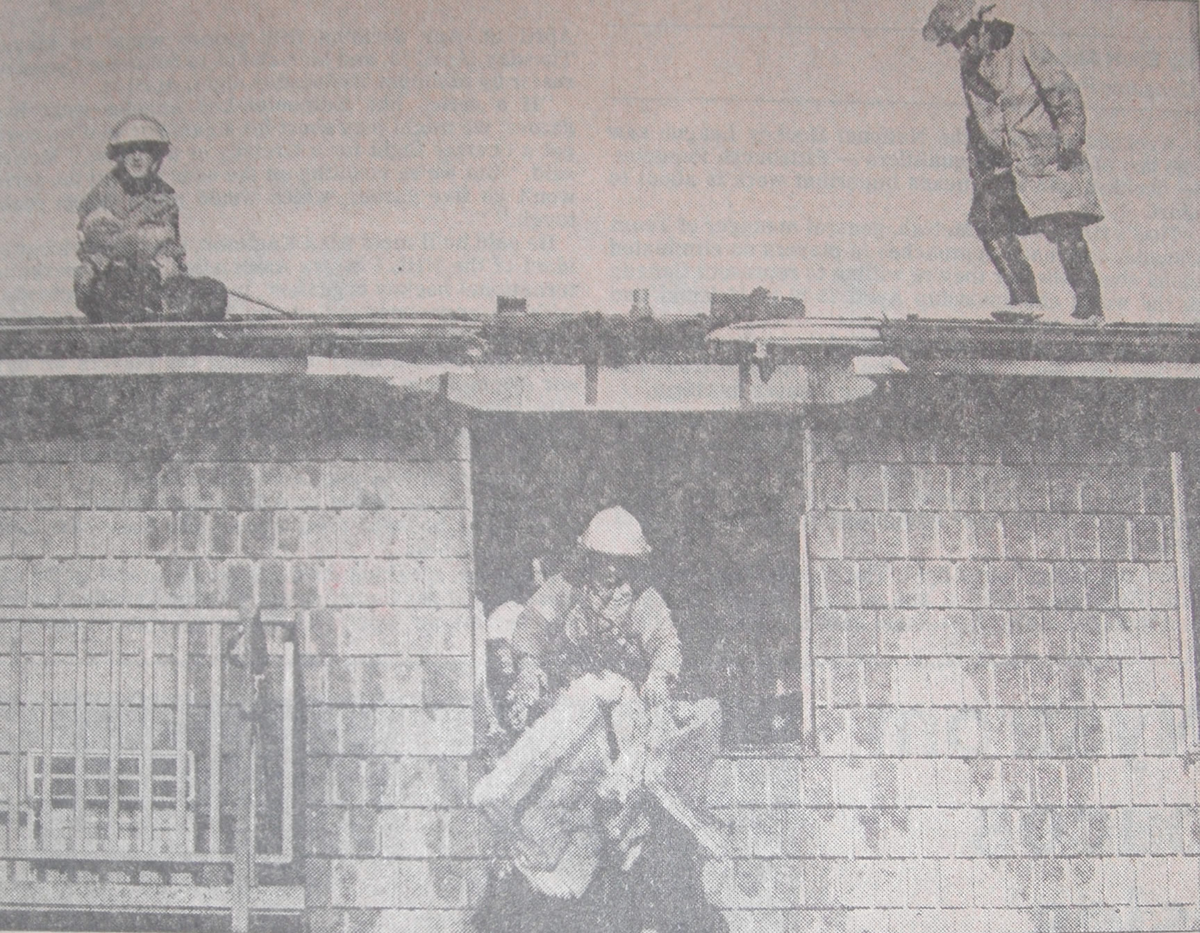 Firemen drop soggy chunks of insulation from the third-storey