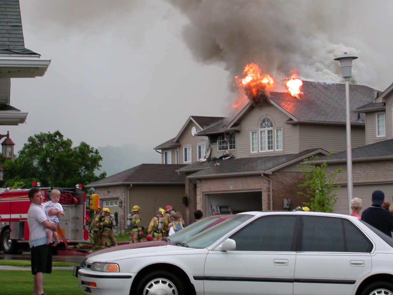 Garage roof on fire, fire fighters gathering to attack garage roof fire.