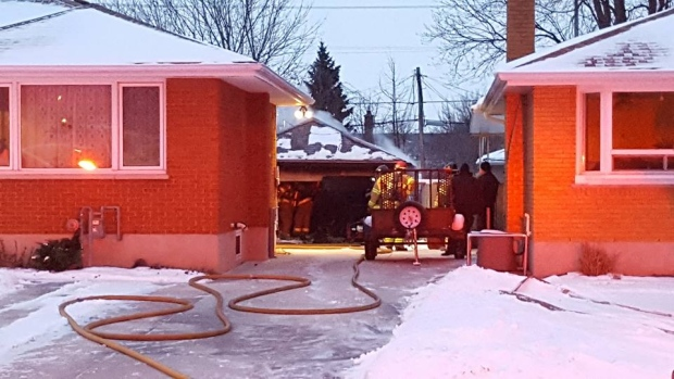 Hose stretches up a driveway to an extinguished garage fire