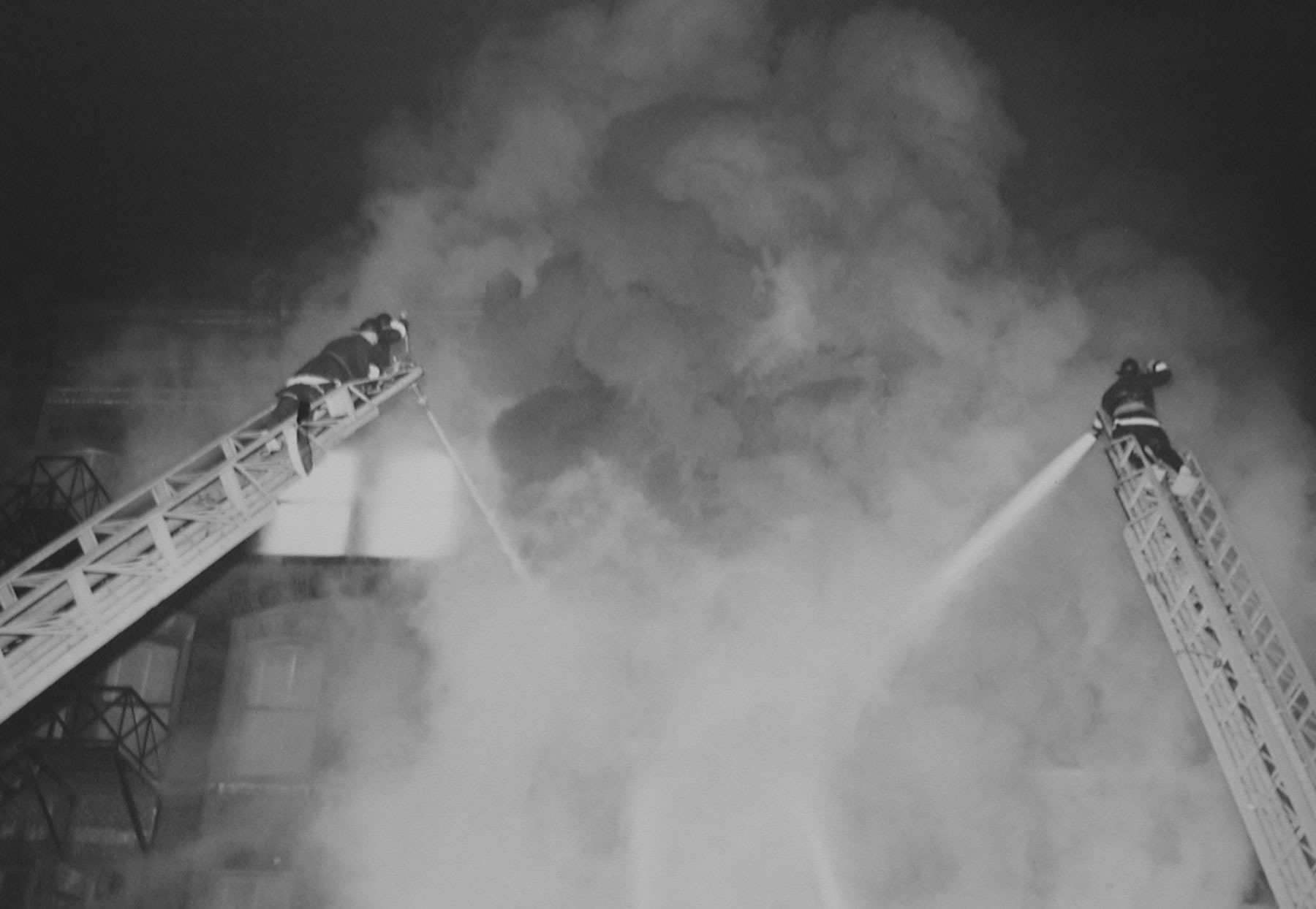 Two large aerial ladders set-up with as firefighter on each spraying water on the very large fire through the smoke.