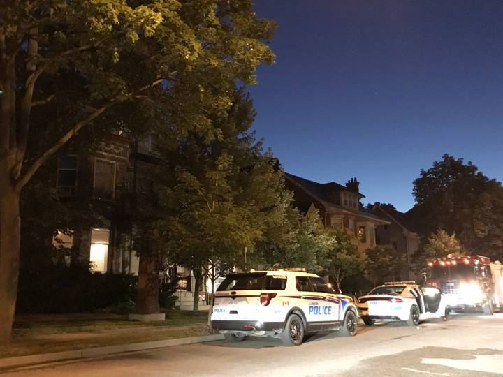 Police cars parked in front of house fire