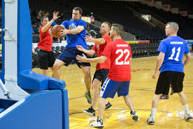 Three firefighters prevent a police officer from scoring in the basketball game