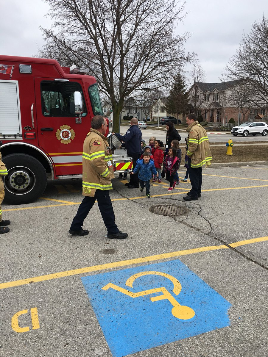 Fire fighters showing the fire engine to public school students