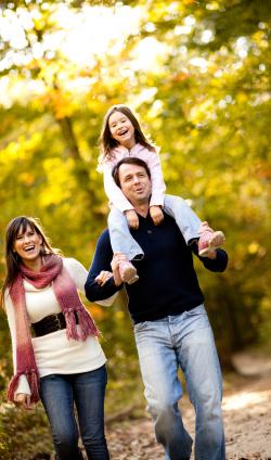 family-of-three-walking-through-autumn-woods