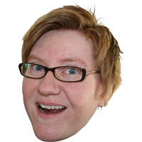 Cyndi's head with no background. She is smiling, wears glasses, has short, red hair.