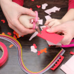 hands cutting paper for Pinterest Valentine's crafts