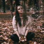 Sad woman sitting on leaves disintegrating