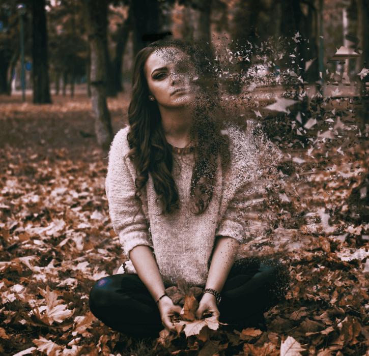 Sad woman sitting on leaves disintegrating