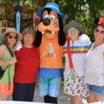 family with Goofy on vacation at Disney world