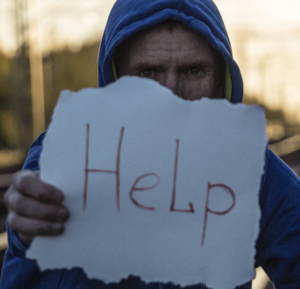 Man with sign asking for HELP