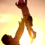 Parent tossing child in the air and catching her - Trauma-Informed Parentin