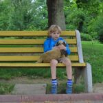 little boy with blond hair in shorts and blue jacket sitting alone on bench holding stuffed animal