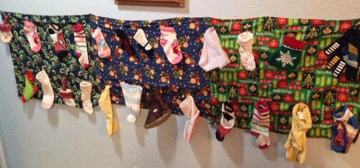 advent calendar made of socks, hats, gloves hanging on blanket on wall