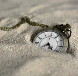 picture of roman numeral pocket watch in sand