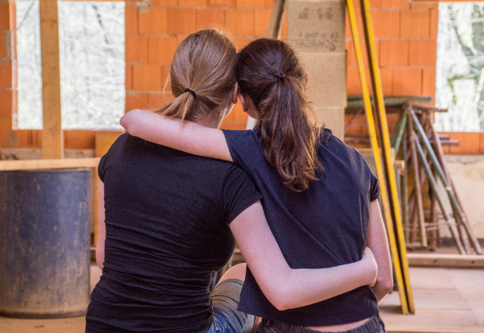 Two women hugging and leaning on each other
