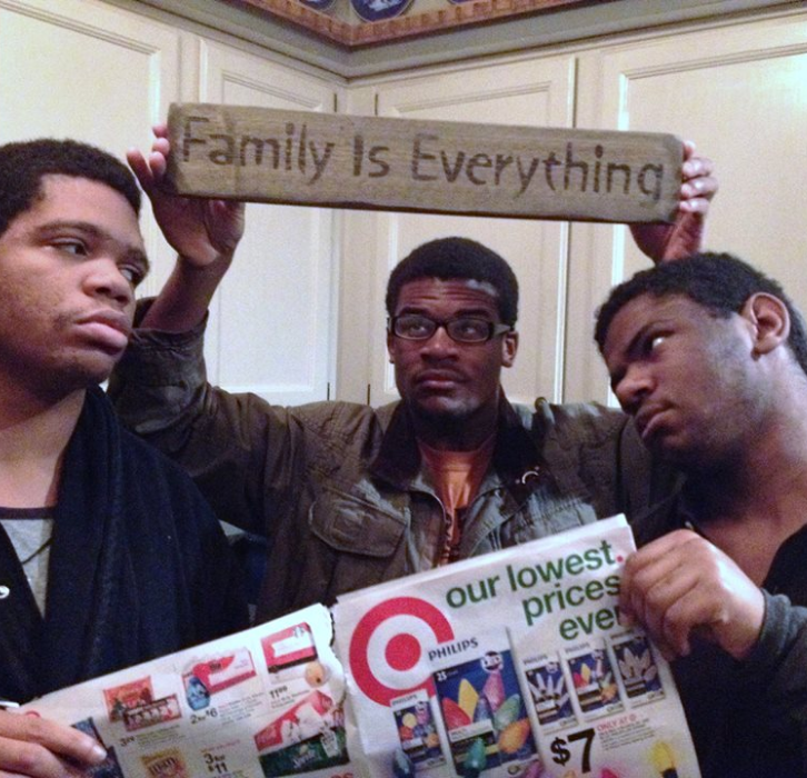 """three young men with Target ad and """"family is everything"""" sign"""