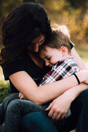 mother holding and comforting young boy