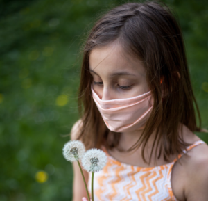 lonely girl wearing dress and mask holding dandelions