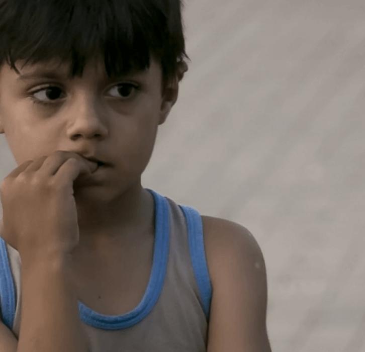 sad boy alone in a corner chewing finger