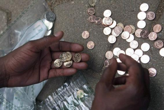 """A Zimbabwean street vendor sorts new coins in front of a bank in Harare, December 18, 2014. Reserve Bank of Zimbabwe governor John Mangudya introduced the new """"bond coins"""" in December 2014. REUTERS/Philimon Bulawayo"""