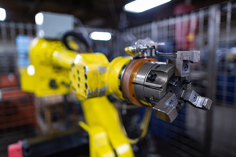 Close up of yellow robotic arm.