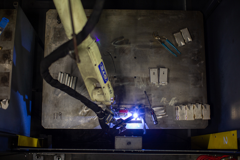 Robotic mig welding of steel parts in a  custom weldment for the material handling industry .