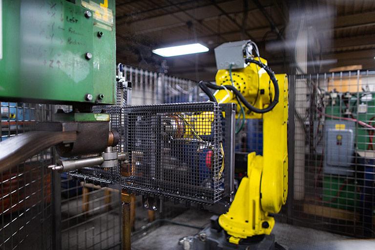 Robot welds industrial heat treating wire basket.