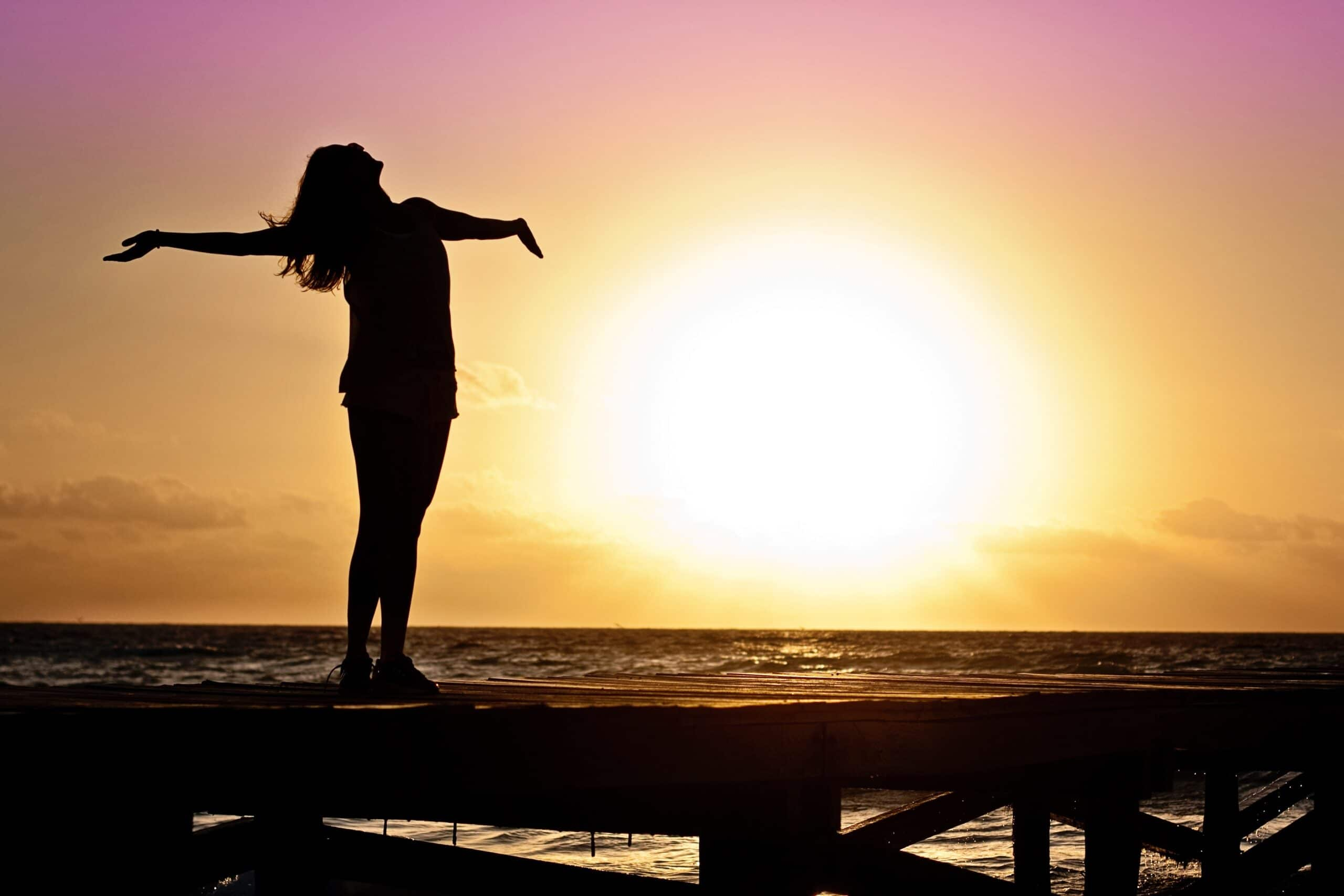Female embracing the sunset on a dock to represent life coaching San Antonio
