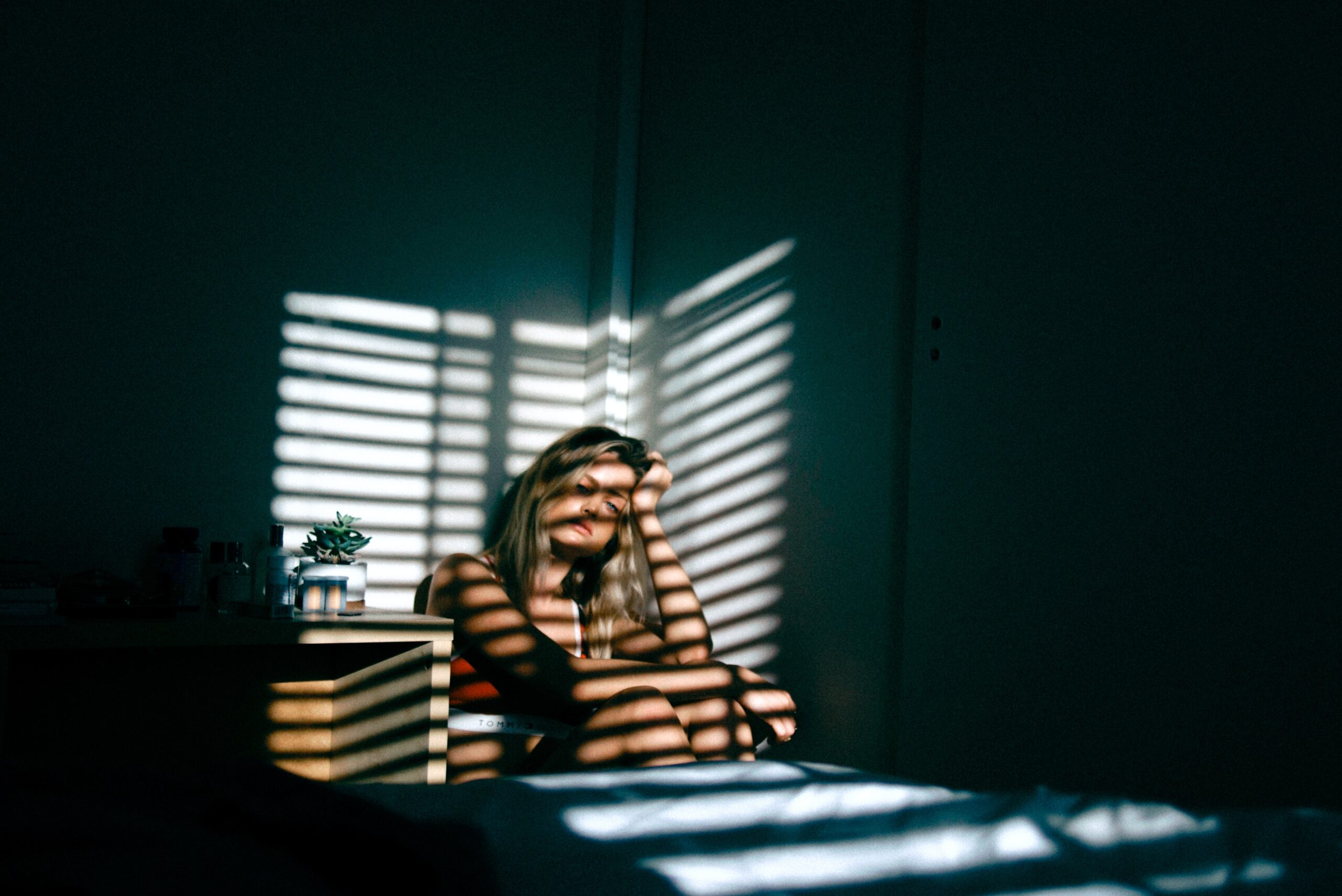 Woman grieving in a dark room to represent depression therapy in San Antonio, TX