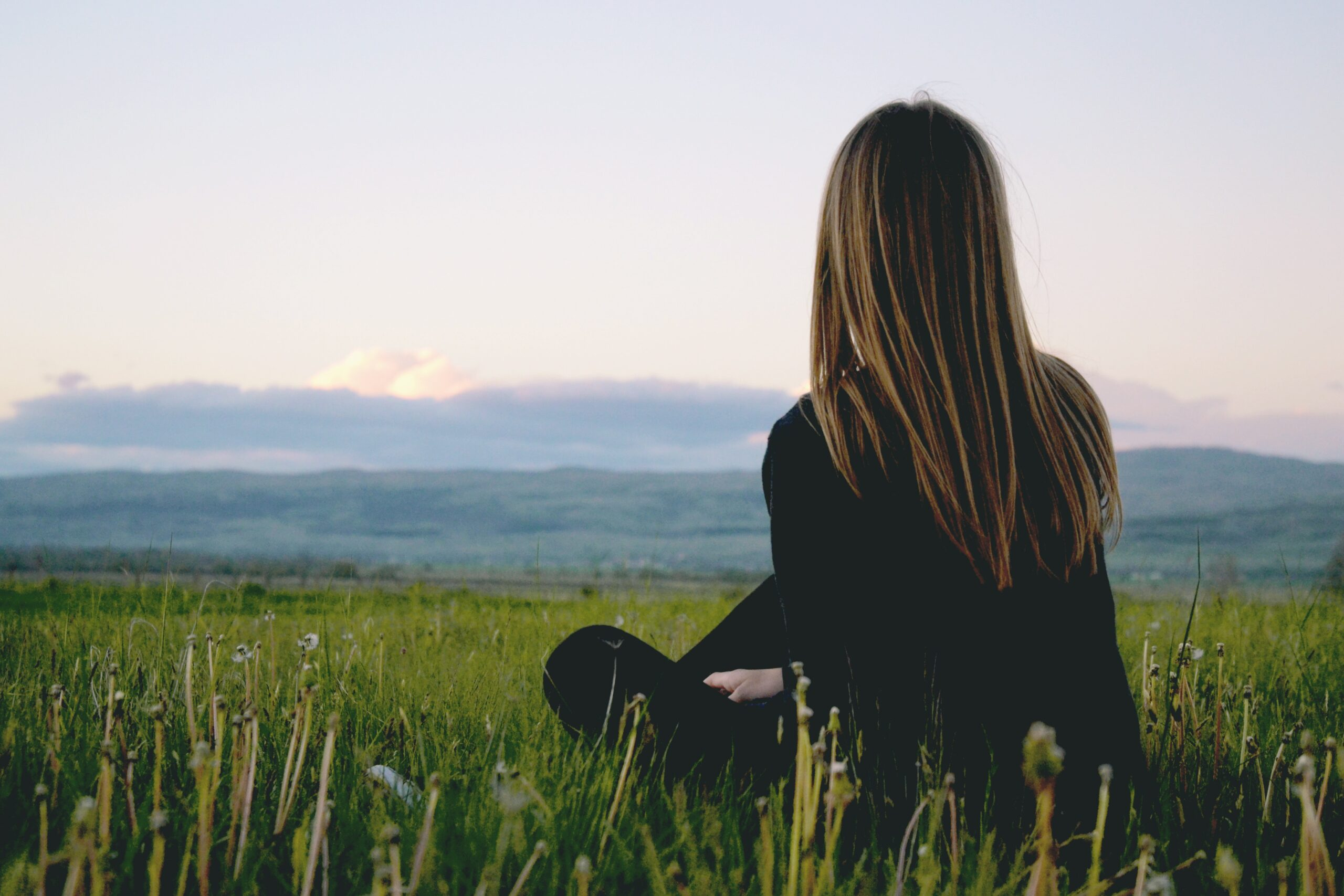 woman in a field looking at mountains to represent depression counseling in san antonio