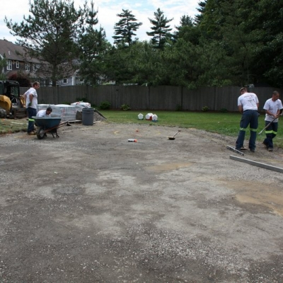 Before large patio, firepit, and seating wall with piers 4