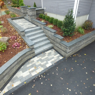 Artline French Grey and Winter Marvel blend pavers with a Basalt Copthorn Exterior border. Lineo granite wall with a Charcoal accent and Blue Mist coping. Granite steps. Low Voltage lighting