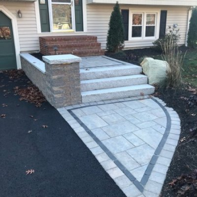 Entrance with retaining/ seating wall, granite steps, and lighting