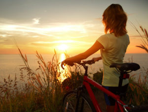 woman on a bike at sunset