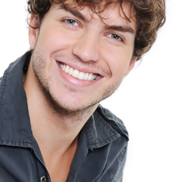 Happy smile and healthy teeth on the face of young man over white