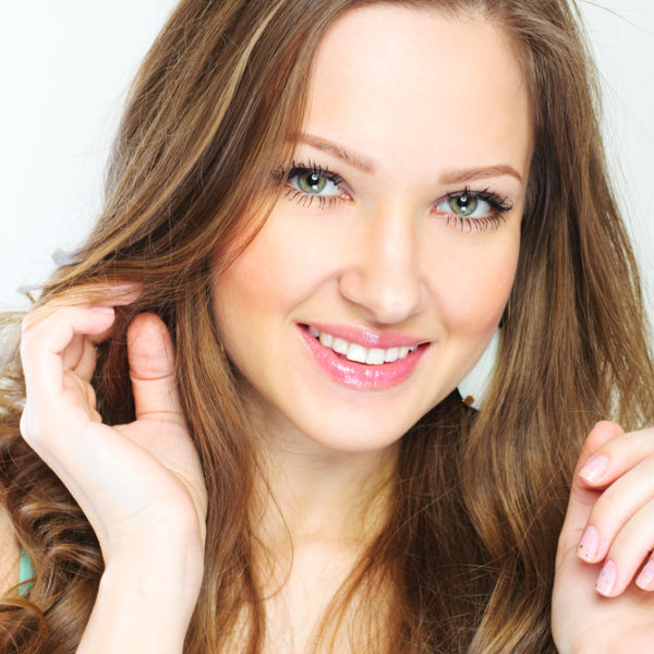 closeup portrait of a beautiful young woman with curly long hair