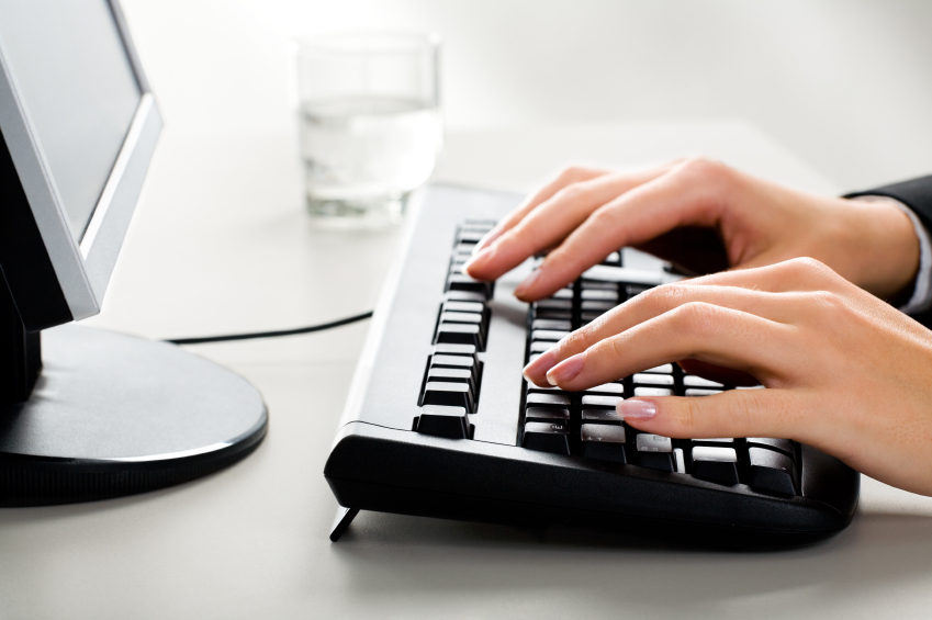 Photo of female hands on the keyboard of computer typing a letter